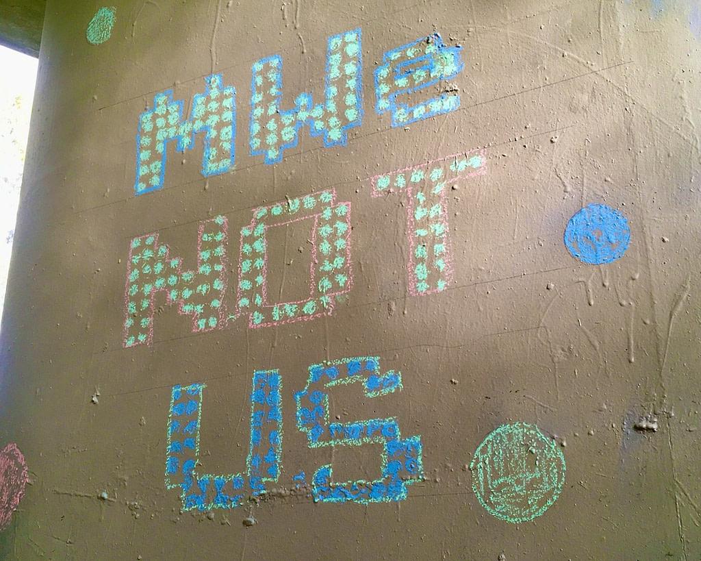 Example of long game meme: 'MWe not Us' in chalk on pillar