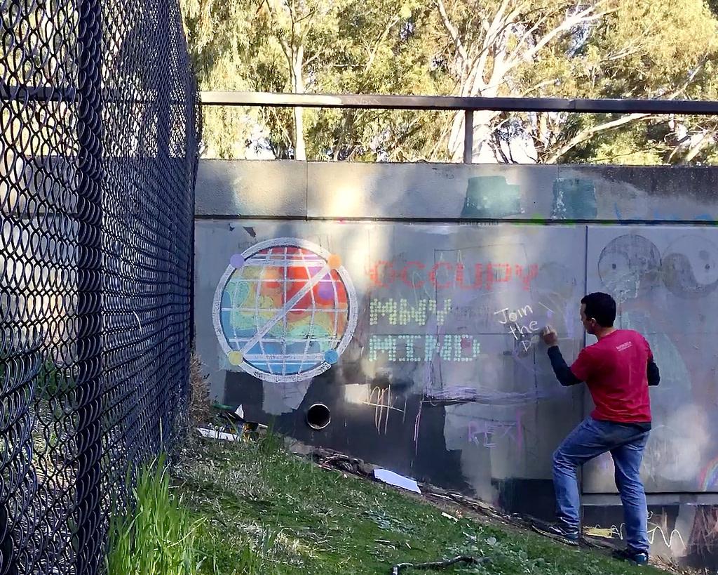 Chalk Wall: Man chalking 'Occupy MWy Mind'