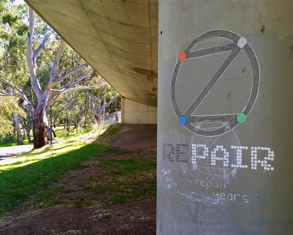 Example of Long Game Meme: 'Repair' and dotZero in chalk on pillar