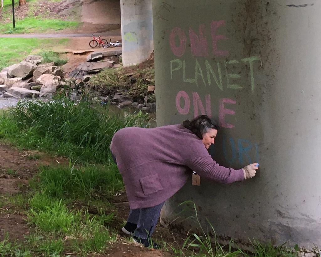 Woman chalking 'One Planet, One Future' on pillar