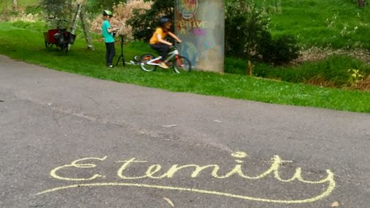 Example: Eternity, written in chalk, children in background