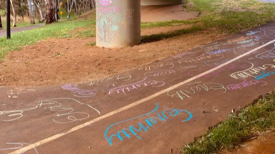 Example: Eternity repeatedly written in chalk on walkway. Colurful pillar in background.
