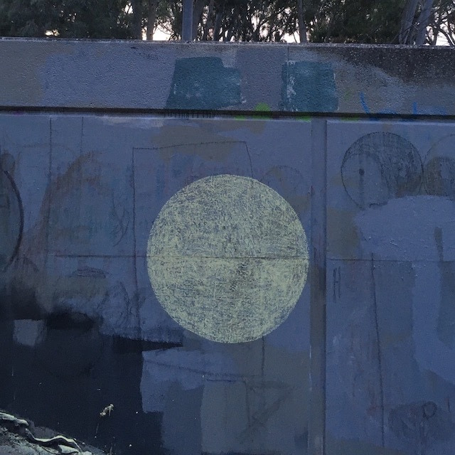 Large yellow chalk dots on wall. Faded chalk graffiti and ying yang in background.