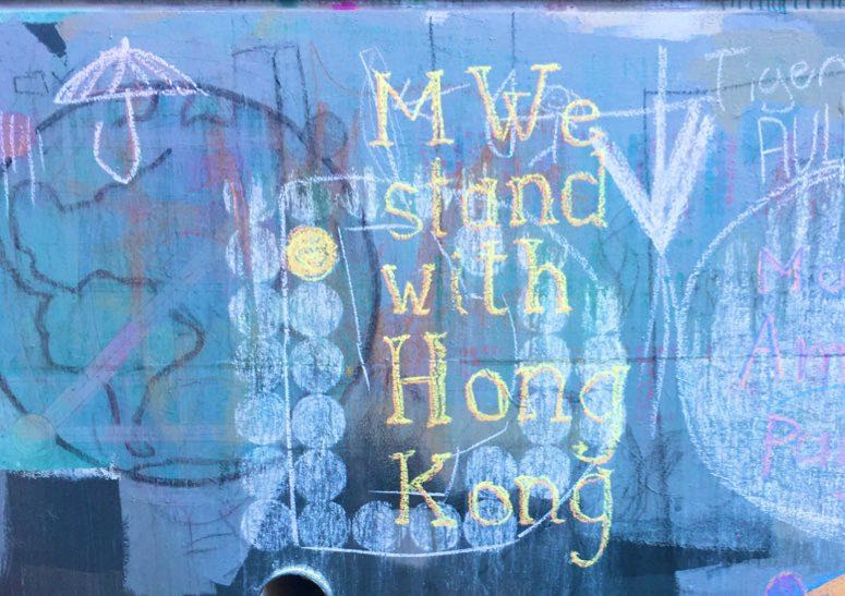 Example: 'MWe Stand with Hong Kong' in chalk, with umbrella