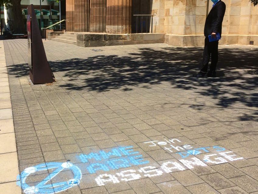 Example 'MWe Are Assange' in chalk, at courthouse